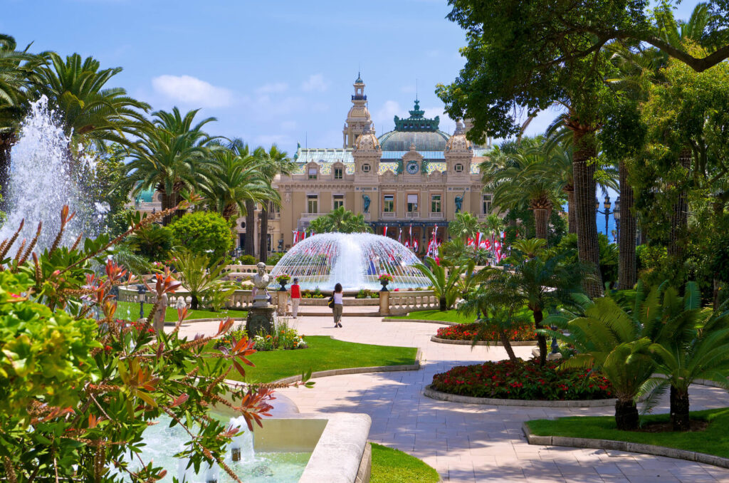 A photograph showing a large mansion and gardens in Monaco. It includes beautiful palm trees, a large fountain, and various shrubs