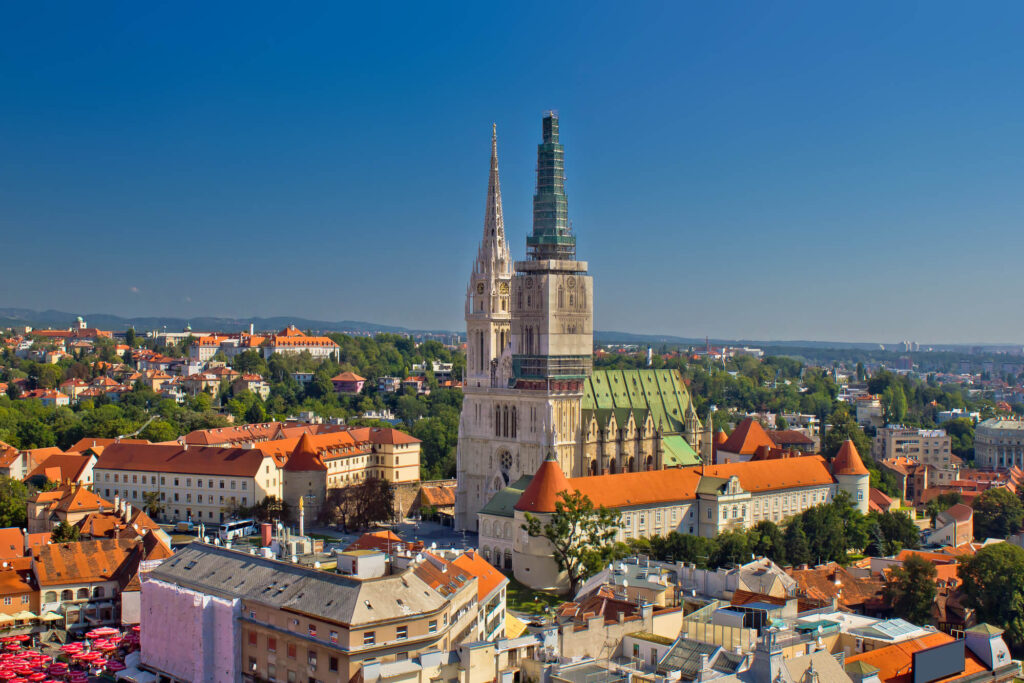 A picture of Zagreb Croatia showing the main church and other historic old buildings. There are tree lined streets, a blue sky and hills in the distance