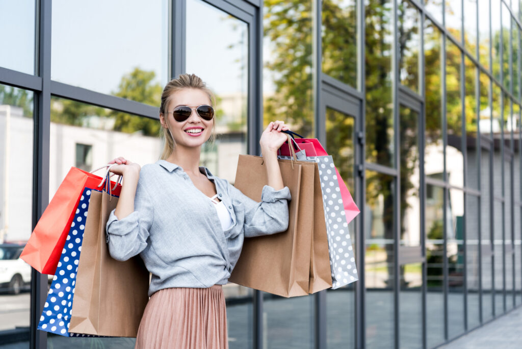 A picture of a young blonde woman holding shopping bags and standing in front of a shopping centre in Florida
