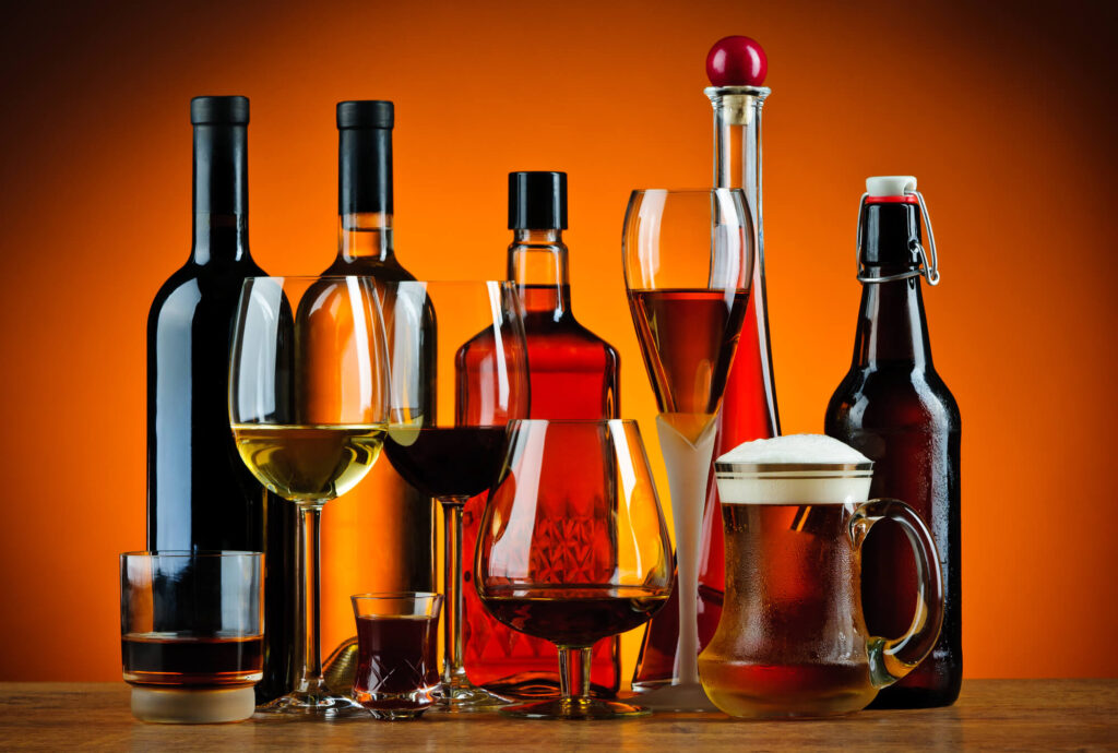 A picture of various bottles and glasses containing alcoholic drinks including wine, beer, and spirits