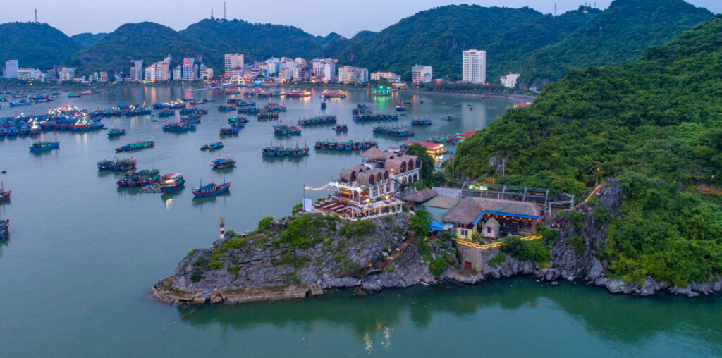 An aerial photo of Cat Ba island, Lan Ha bay. Hai phong, Vietnam. It shows a large restaurant on a rocky outcrop, the bay, a number of boats and several houses