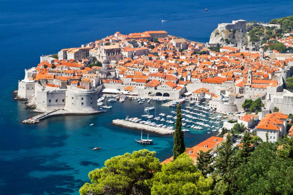 An aerial  photograph of The Old Town of Dubrovnik in Croatia. It shows dozens of white walled buildings with orange terracotta tiles. The city is surrounded by blue ocean water