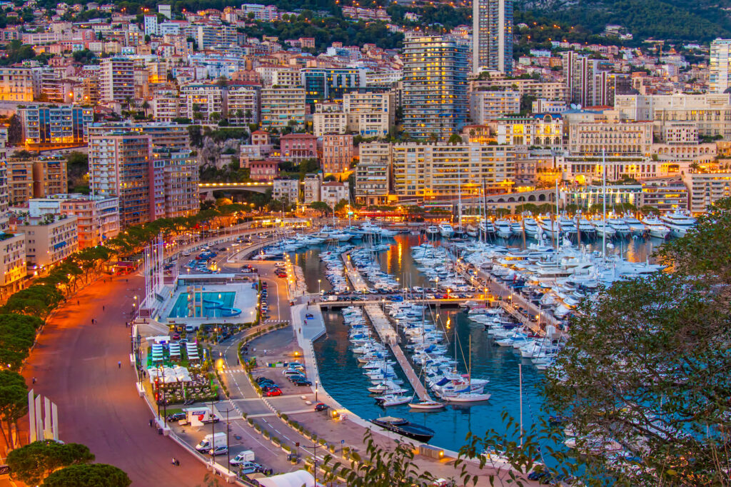 An aerial photograph of the Principality of Monaco in the early evening. The image shows the port and residential area