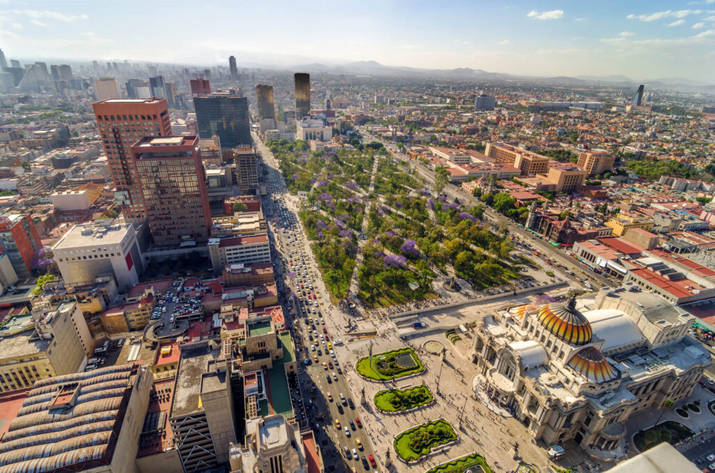 An aerial shot of Mexico City. It shows a large central park, several skyscrapers on the left, a large domed building in the bottom of the frame, and hundreds of homes on the upper right of the image
