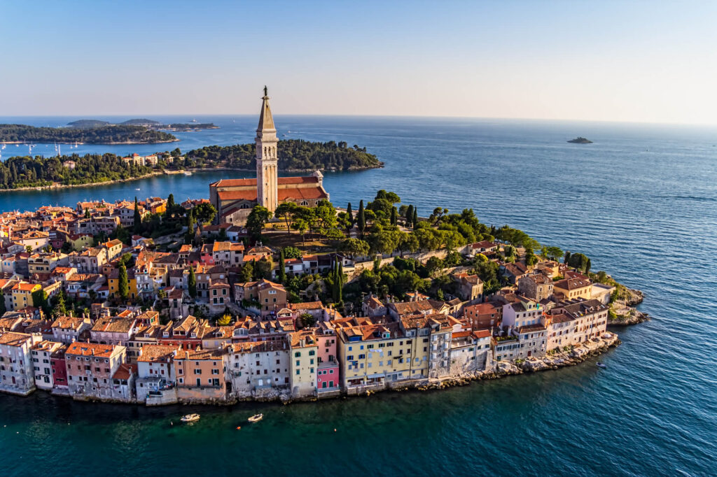 An aerial shot of Rovinj, Croatia. It shows several large outcroppings of land surrounded by blue ocean. The city features dozens of tightly packed rustic buiildings surrounding a large church