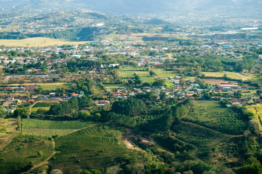 An aerial view of San Jose in Costa Rica showing a few dozen houses, open green pastures, trees, and a series of hills