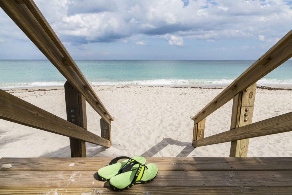An iage showing a pair of flip flops on a deck with a beach and calm blue ocean