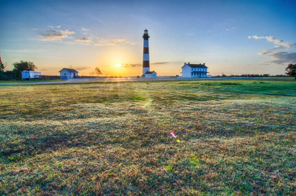 An image of Bodie Island Lighthouse OBX Cape Hatteras North Carolina. It shows the sun rising over a green landscape with a lighthouse and several farm houses