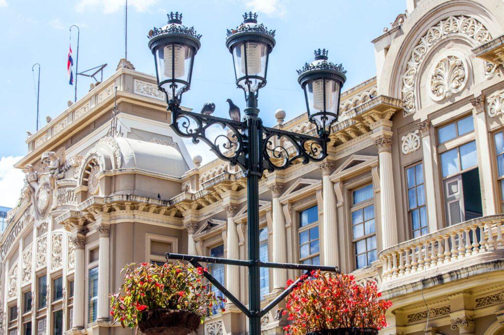 An image of Edificio Correos in San Josem Costa Rica. It shows a lamp, an ornate white building, and a blue sky