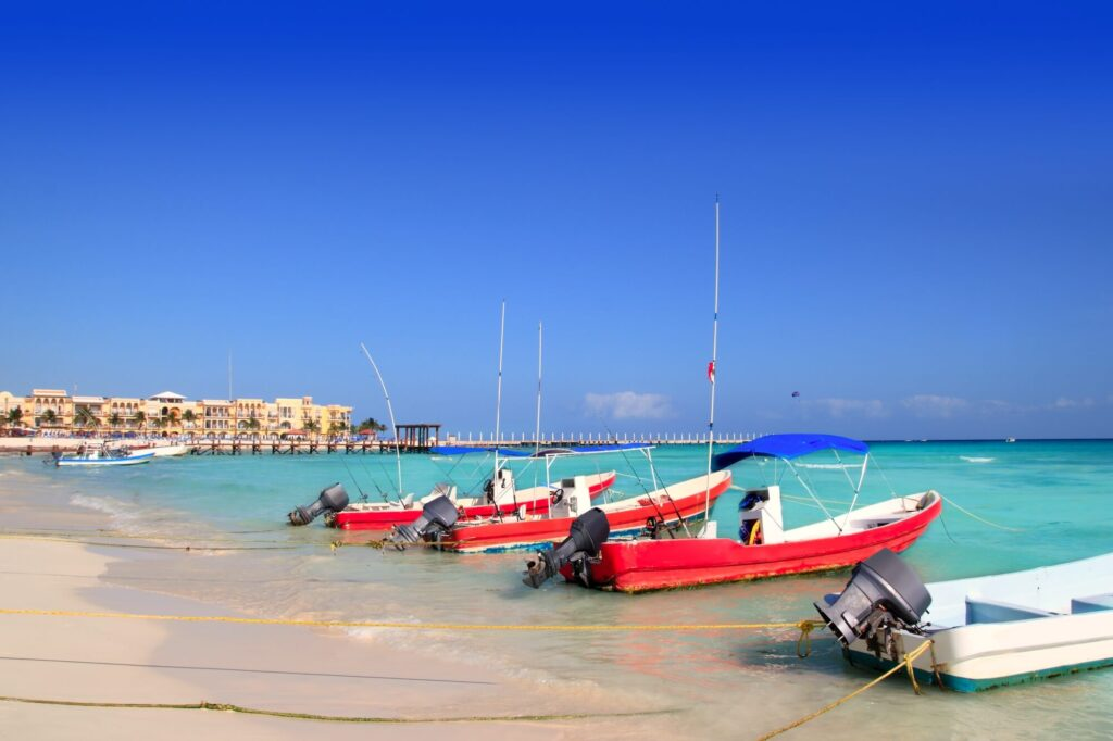 An image of Playa del Carmen in mexico, showing a white sandy beach, aqua blue ocean water and several boats
