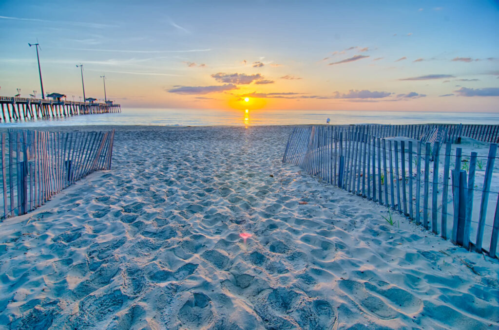An image of a beach on the Outer Banks at dawn. It shows a picket beach fence leading down to a wide beach, tranquil water, a large dock on the left, and an orange sun rising in the east