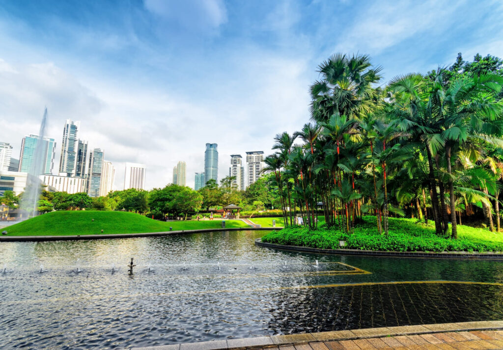 An image of a beautiful park in Kuala Lumpur. It shows a large clear pond, a footpath, grass, and several palm trees. In the distance, you can see several Kuala Lumpur high rises