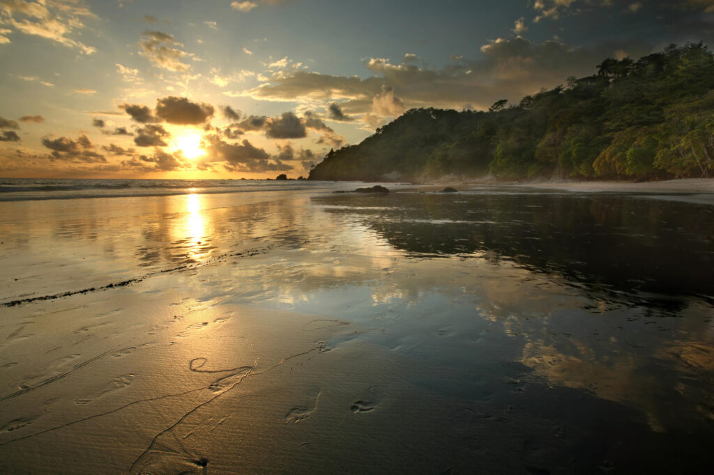 An image of a sunset on a beach in Costa Rica. It shows a wide sandy beach, orange sun hitting the horizon, and an a hill lined with trees to the right