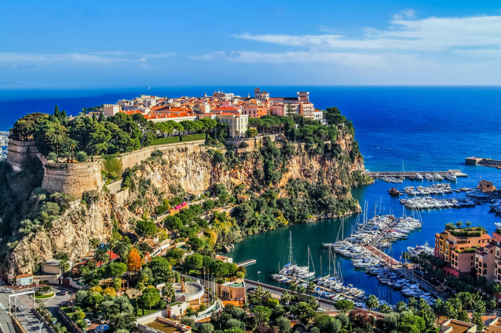 An image of principaute of monaco and monte carlo. It shows a high rocky outcropping covered in buildings and a bay with dozens of yachts