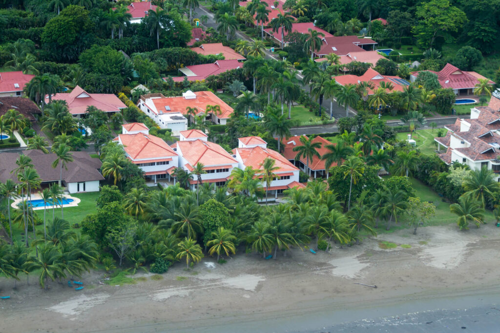 An image of the coastline of Costa Rica, showig several large homes with terracotta tile roofs and while walls. The homes are surrounded by dozens of palm trees