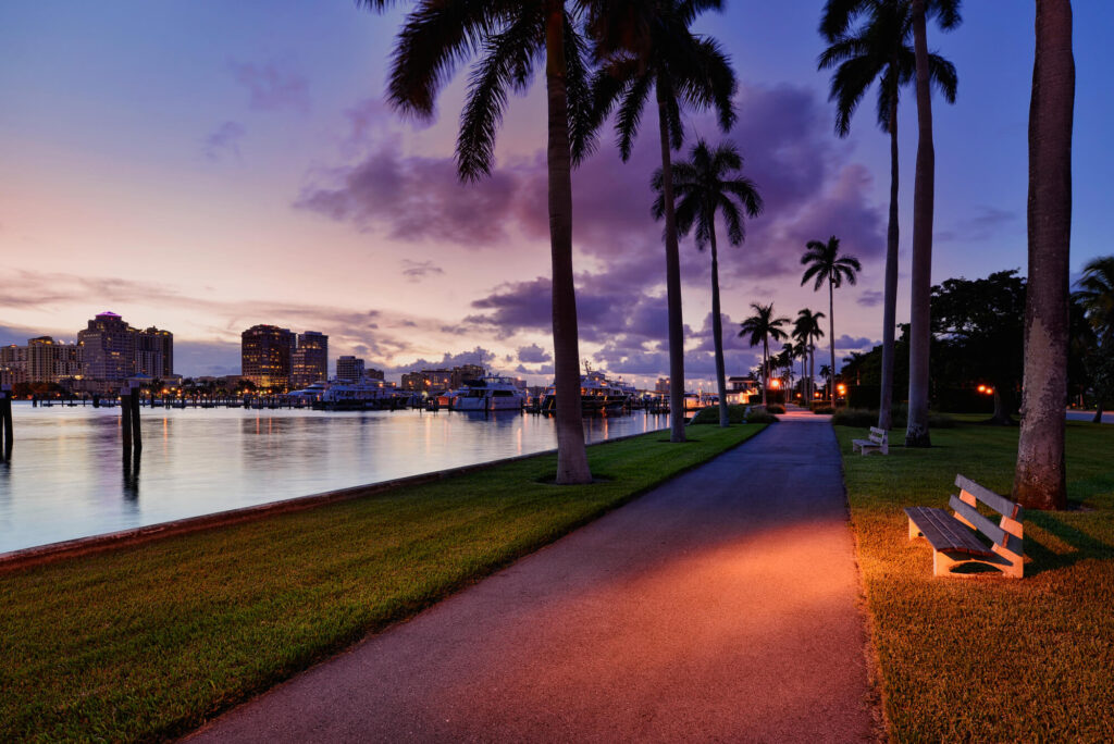 An image showing Palm Beach, Florida in the early evening. It shows a marina full of boats and several high rises