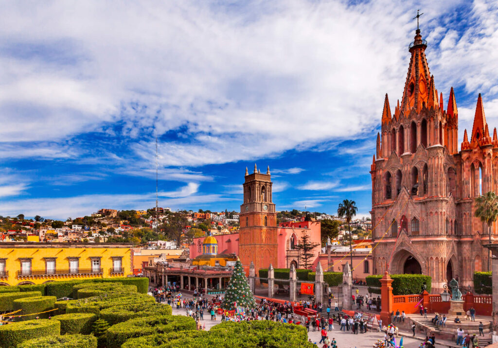 An image showing Parroquia Jardin Archangel Church in San Miguelm Mexico. It shows a large brick church, a colourful yellow building and a large garden