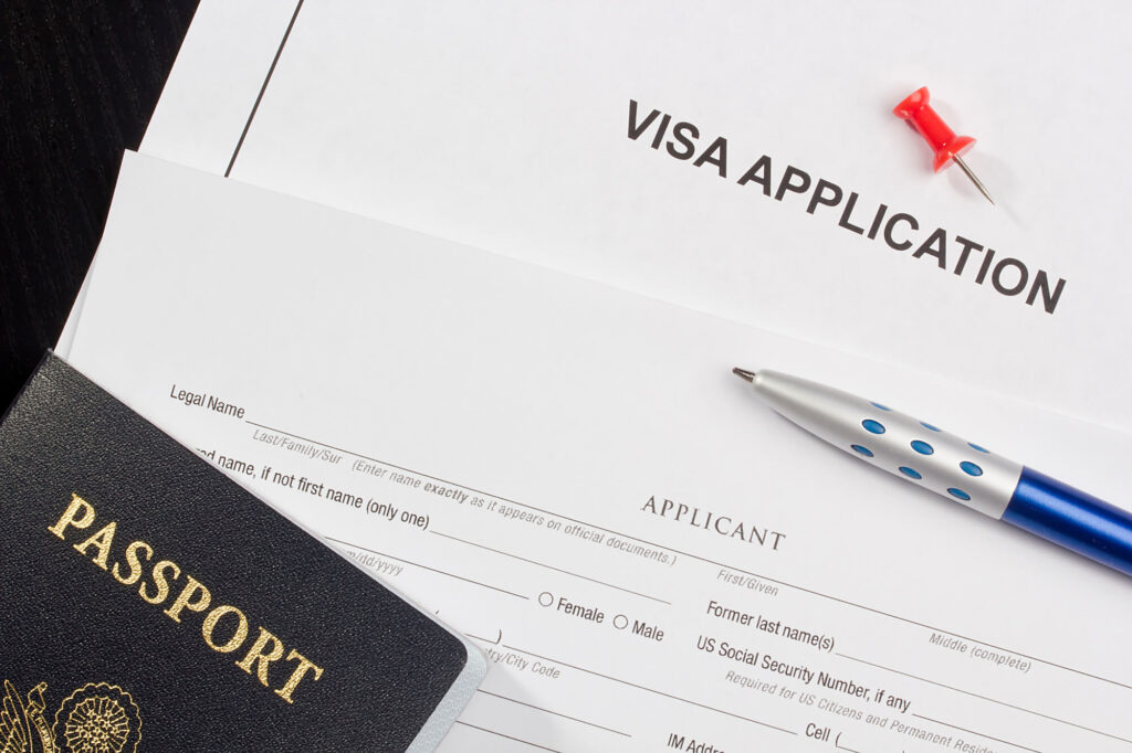 An image showing a VISA application form, a passport, and a pen