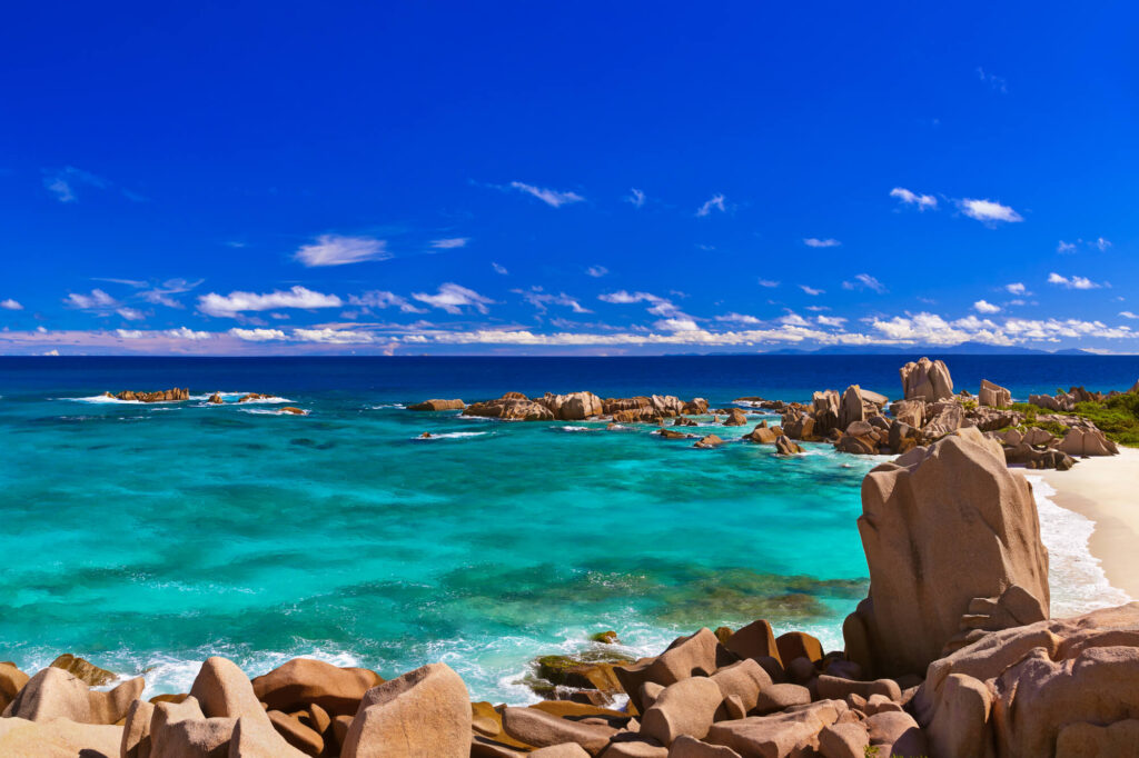 An image showing a beautiful ocean cove in the Seychelles, with crystal clear water, white sand, a blue sky, and large sandstone boulders