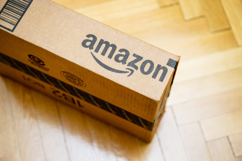 An image showing a cardboard parcel labelled Amazon positioned on a timber floor
