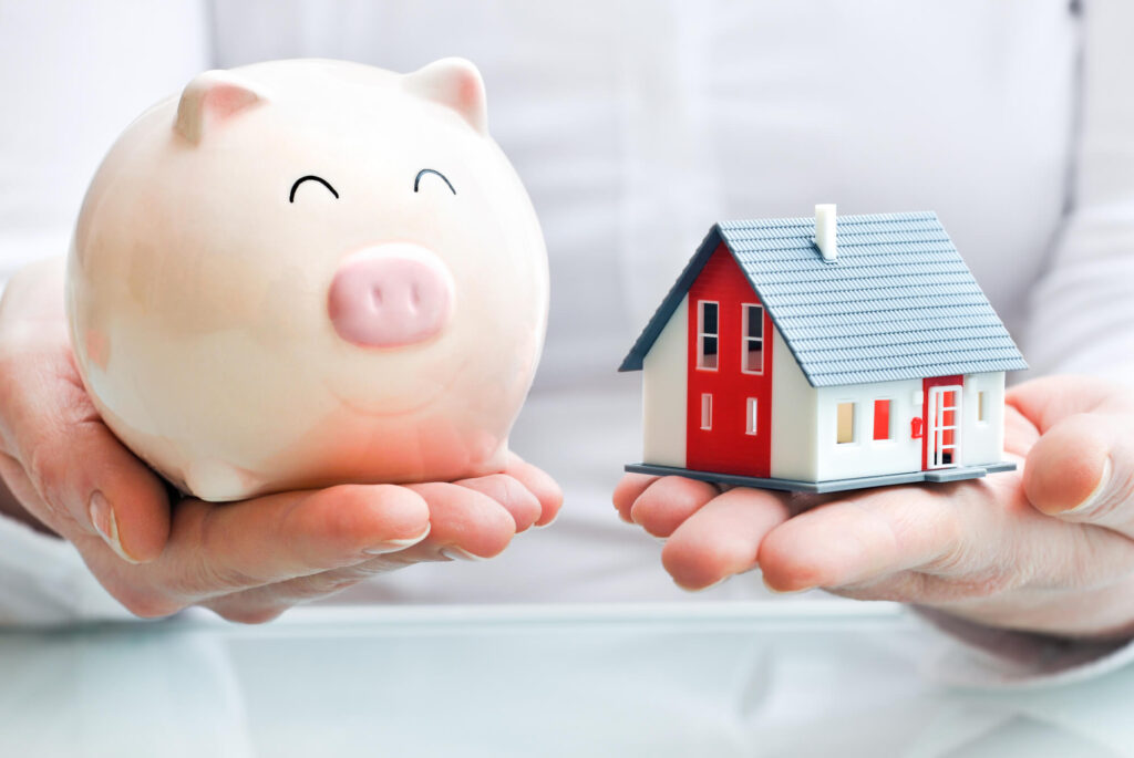 An image showing a person's hands holding a model house in one hand and a piggy bank in the other
