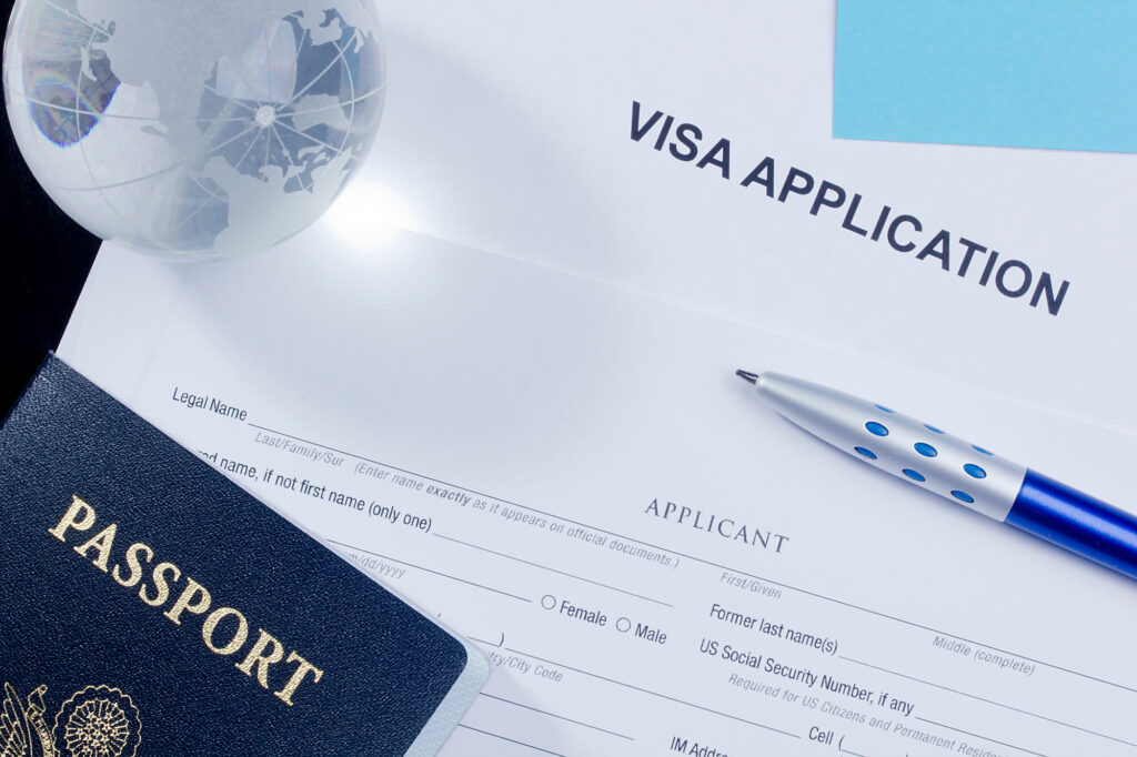An image showing a printed visa application, a pen, and a passport