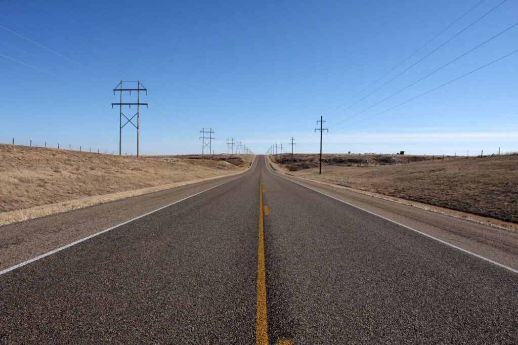 An image showing a very long, empty highway in Texas