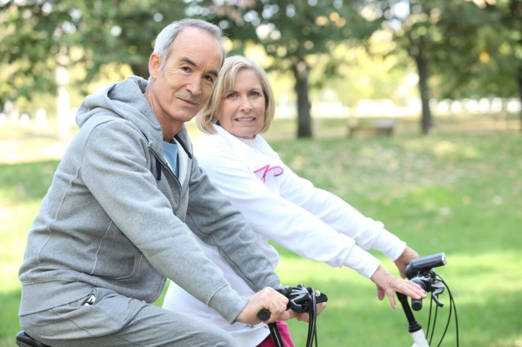 An image showing an older couple look on bicycles who are looking at the camera