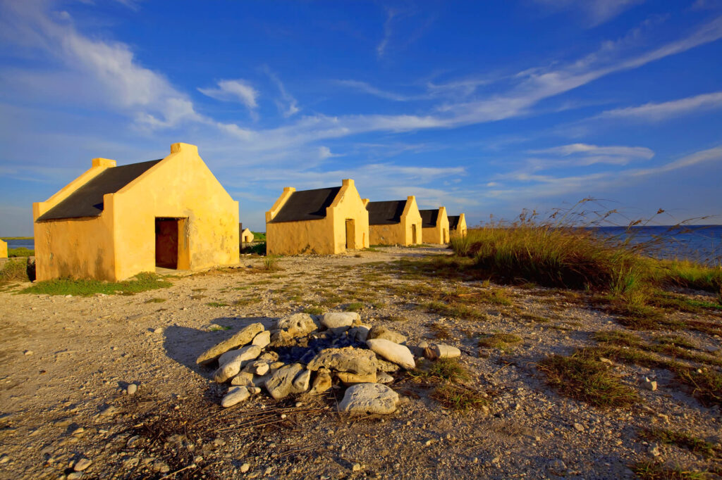 An image showing some old slave huts on  Bonaire. The huts are bright orange and sit on adjacent to the ocean. The sky is bright blue