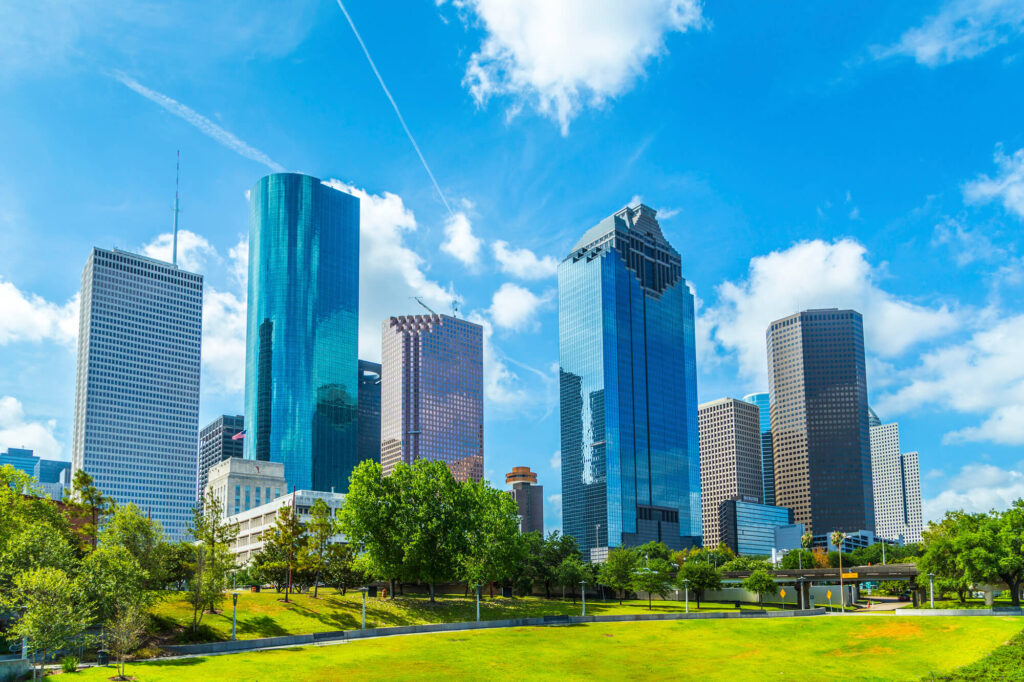 An image showing the Houston skyline during the day. It features a large grassy area, several trees, and high rises in the background