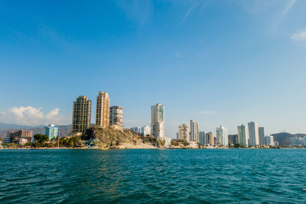 An image showing the city view of Rodadero beach in Santa Marta, Colombia. It features several condos and the shot of a rocky outcrop