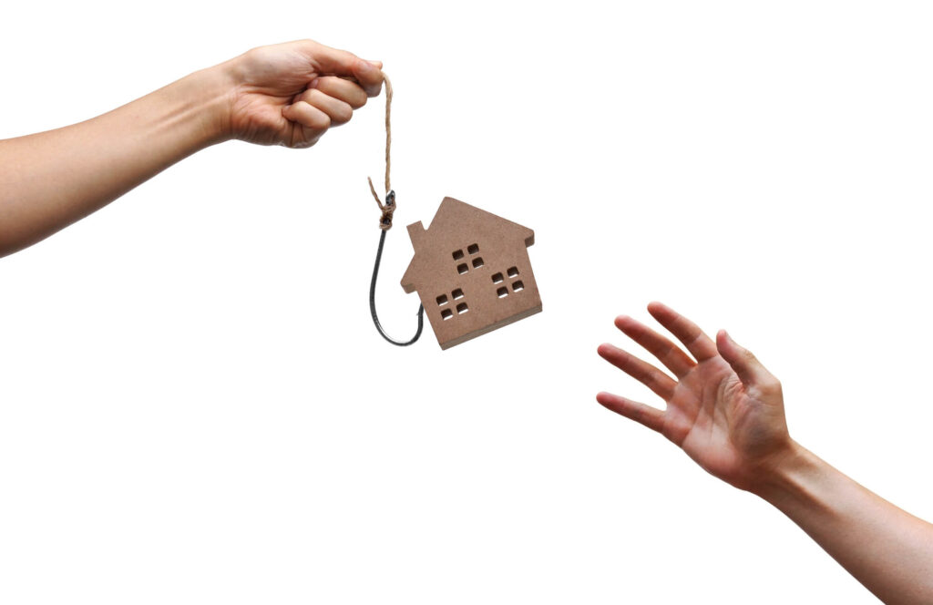 An image showing the hand of a person who is holding a cutout of a house suspend on a hook. Another hand reaches out for it. The image symbolizes the risks of buying property in Malaysia