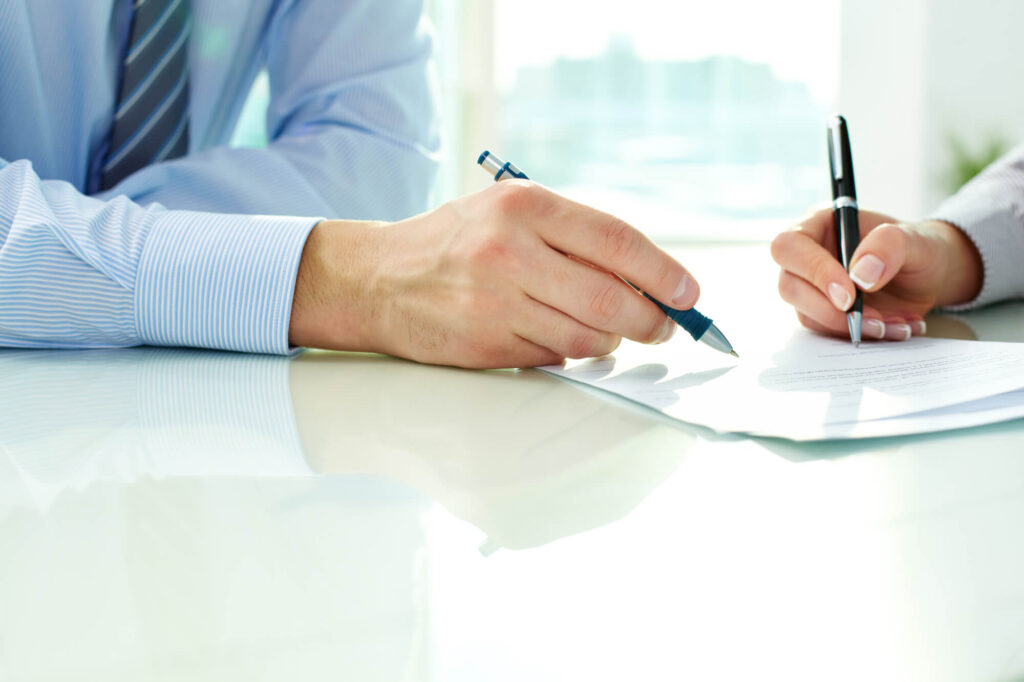 An image showing the hands of a man and woman touching a paper contract, The woman is holding a pen while the man points to an item on the page