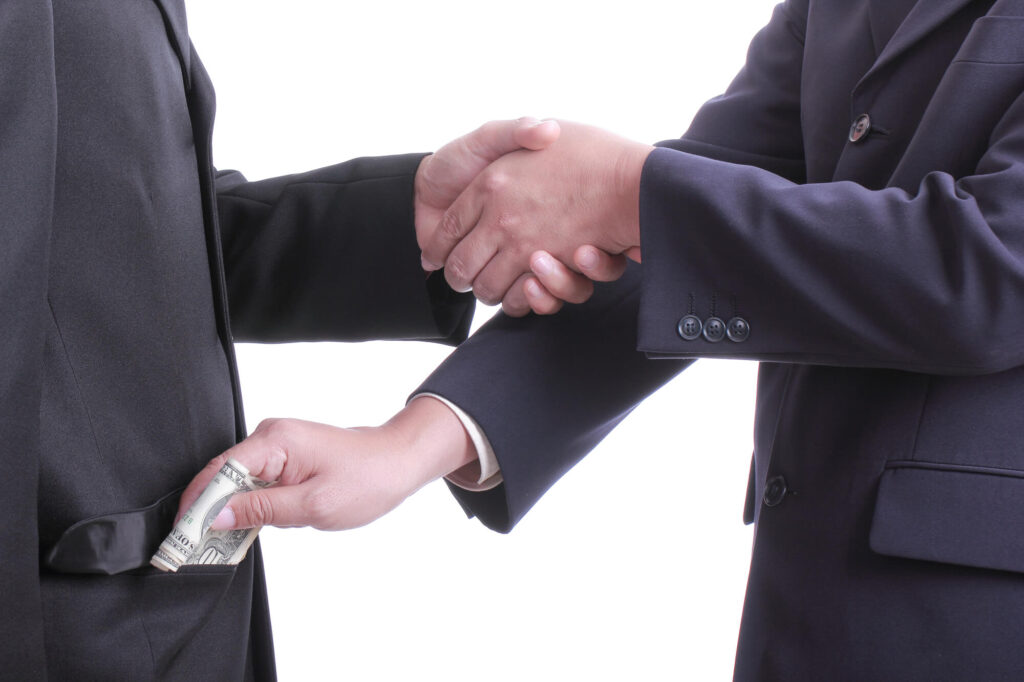 An image showing the torsos of two men in business suits who are shaking hands. As they shake hands, one man is skipping money into the pocket of the other, symbolizing corruption