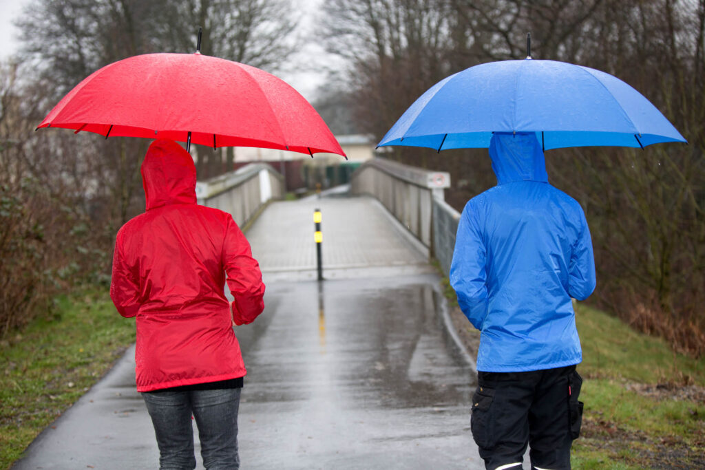 An image showing two people walking towards a bridge in the rain. One person has a red raincoat and red umbrella while the other had a blue coat and umbrella