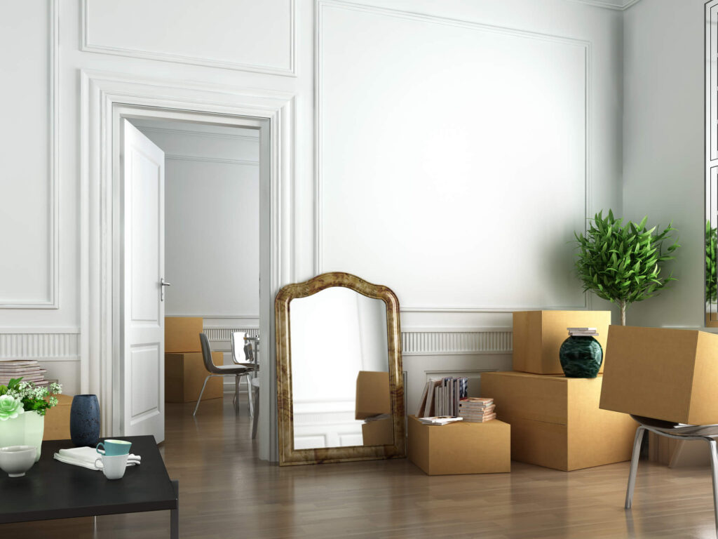 An picture of a apartment with white walls, timber floors and an assortment of moving boxes