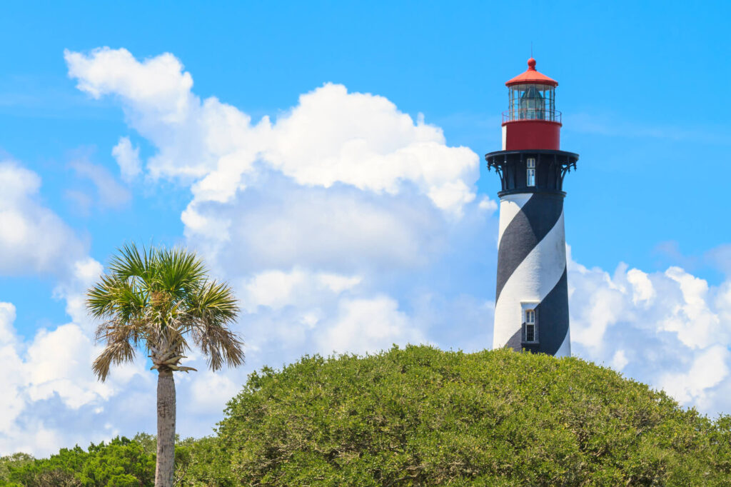 A photo of St. Augustine Lighthouse, in Florida. It shows a vibrant lighthouse which is covered in white and black stripes, with a red center, It is surrounded by green palm trees
