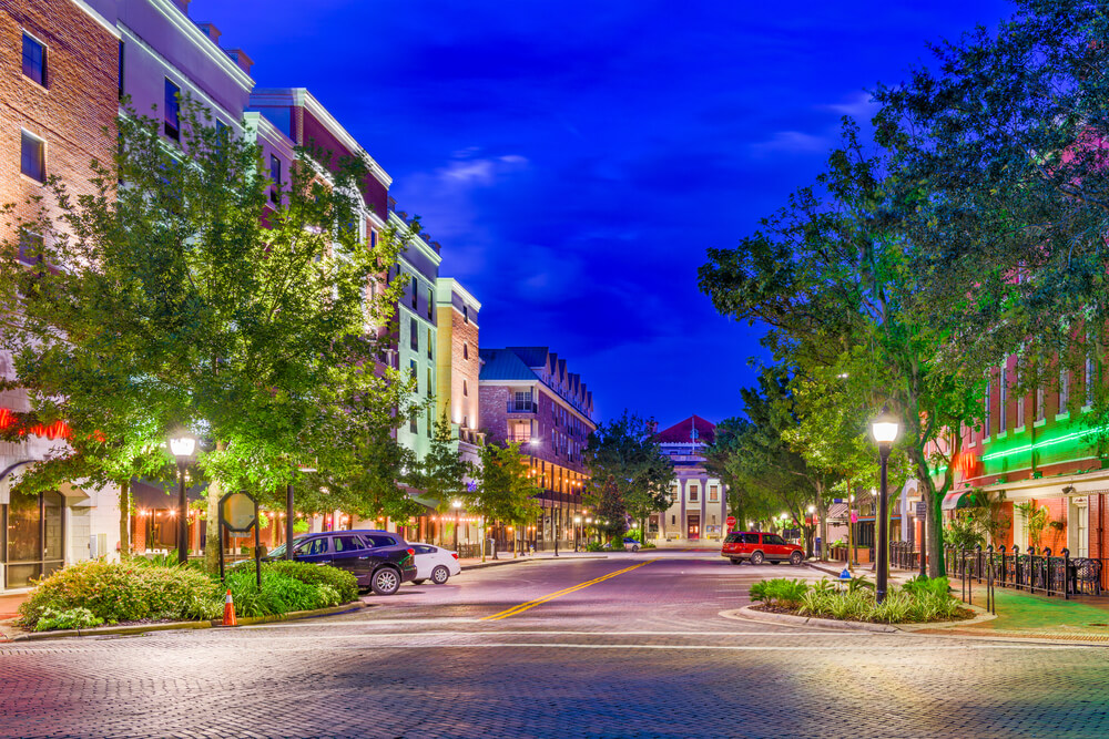 A photo of a Gainsville, Florida street at dusk. It shows a wide street lines with trees and 3 story buildings. The building are very colorful and have shops on the ground floor