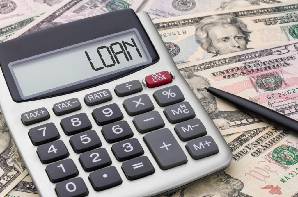 A photo of a calculator with the word loan written on the screen. In the background is a stack of US currency