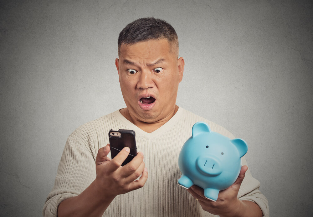 A photo of a man looking shocked as he stares into a mobile phone screen. He has a blue piggy bank under one arm. The image represents bill shock from an expensive mobile phone plan