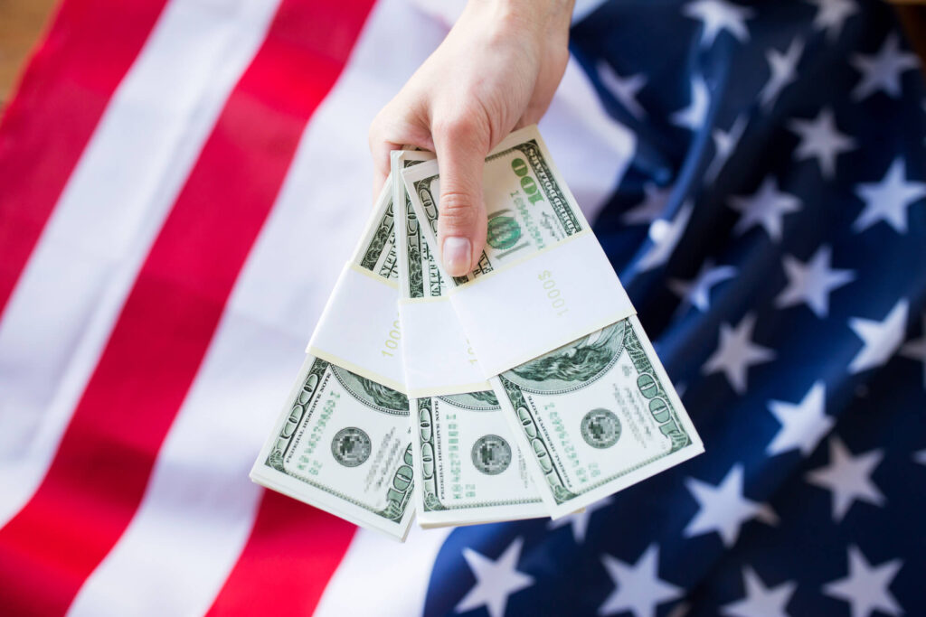 A photo of a person's hand holding 30,000 in U.S. currency. In the background is a blurry image of a U.S. flag