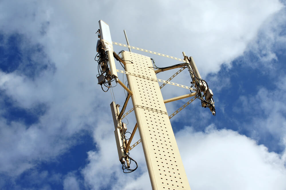 A photo of a telecomunications town shot from the ground up. It shows a blue sky lined with clouds