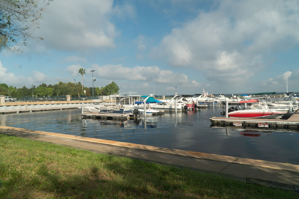 A photo of the habor at Lake Tohopekaliga Osceola County, St Cloud Florida taken in the morning. It shows a large harbor with several boats, a pier and a cloudy blue sky