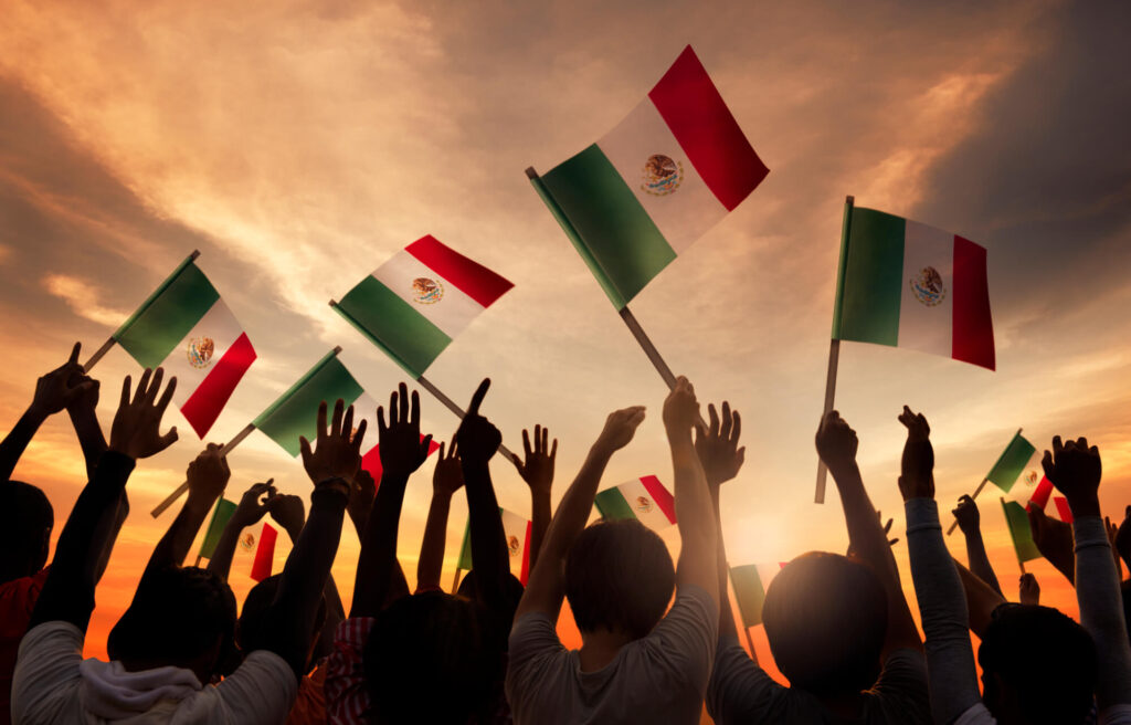 A photo showing a dozen people holding Mexican flags in the air. They are looking away from the camera, into a sunset