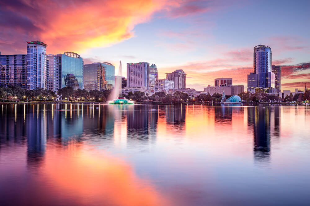 A photograph of Orlando, Florida at dusk. The sun is setting and has made the sky orange. There is a large body of water in the foreground, surrounded by several modern high rises