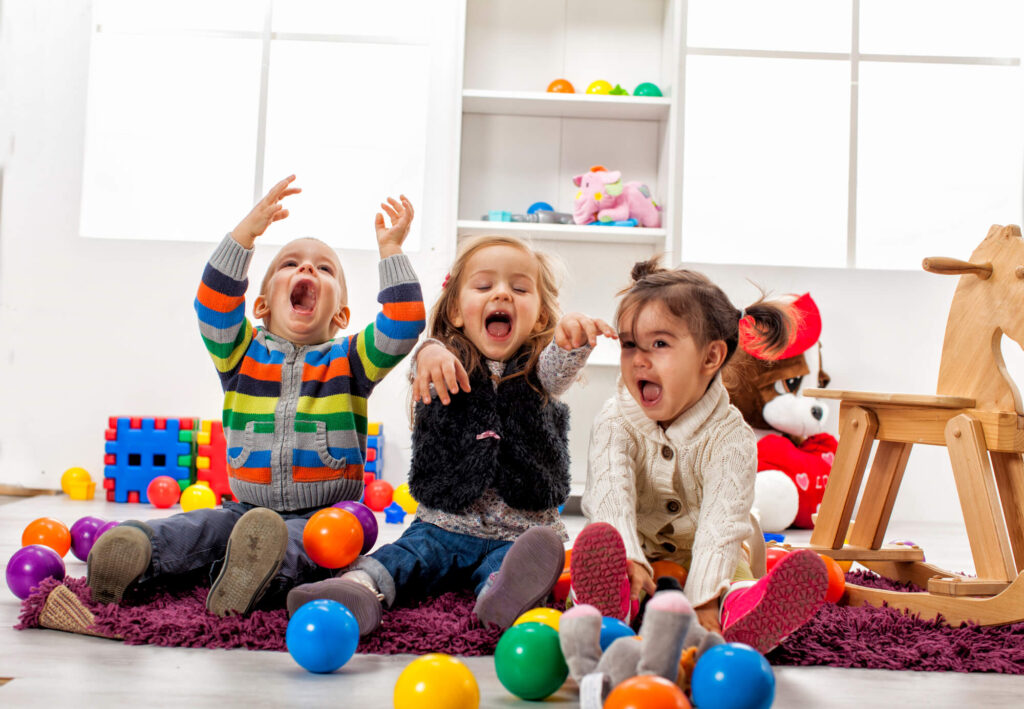 A photograph of three children playing in a day care center. They are throwing colorful balls into the air and screaming in delight
