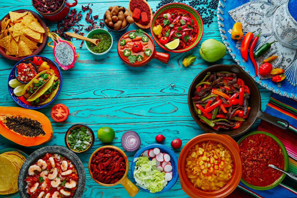 A picture of a huge variety of Mexican dishes positioned on an Aqua colored timber table. Some of the dishes on display include tacos, salad, pranws, salsa, and guacamole