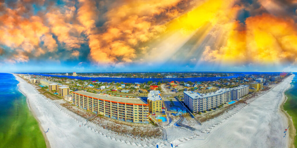 An aerial photograph of Fort Walton Beach, florida, taken using a fish eye lens. It shows a beautiful orange sky, white beaches, deep blue ocean and dozens of condominiums and shops