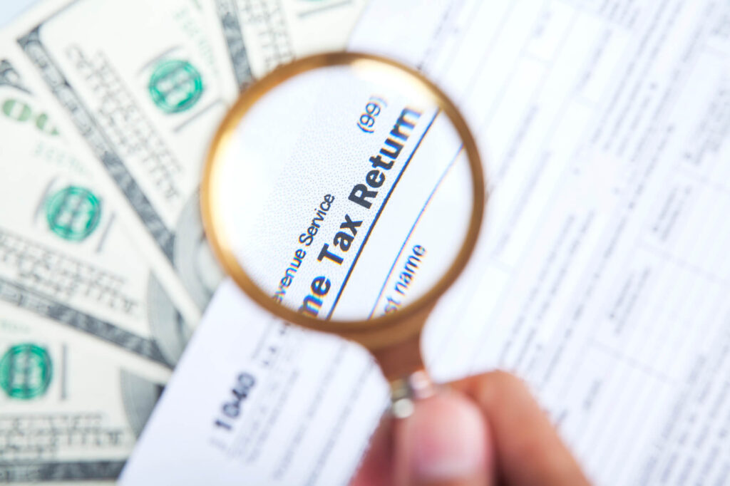 An illustration showing a magnifying glass which highlights the words income tax return on a document