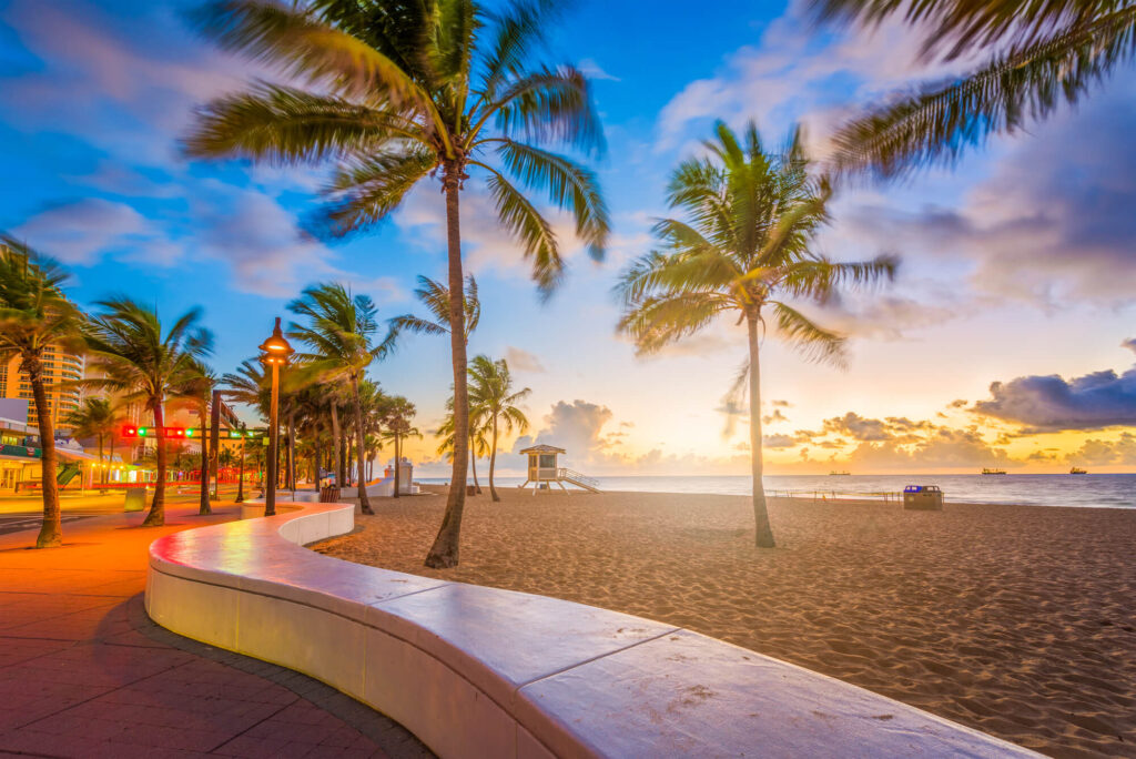 An image of Fort Lauderdale, Florida. It shows a wide sandy beach, several palm trees, a vivid sunset, and a winding footpath. To the left of the image is a number of shops